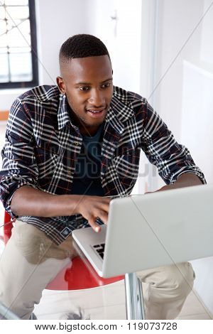 Young African Man Working On Laptop At Home