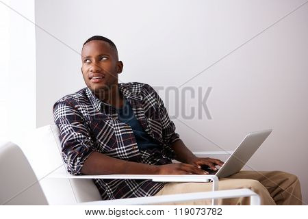 Relaxed Young Man Sitting On Chair With A Laptop
