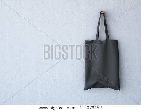 Black cotton bag on the concrete wall. 3d rendering