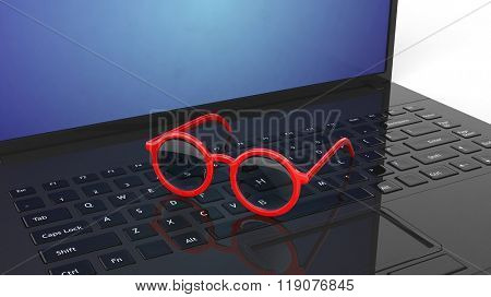 Pair of red round-lens eyeglasses set on laptop keyboard
