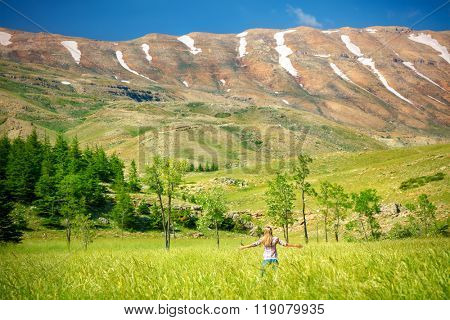 Happy woman standing with raised hands in the fresh green valley near the mountains, enjoying amazing nature of Lebanon