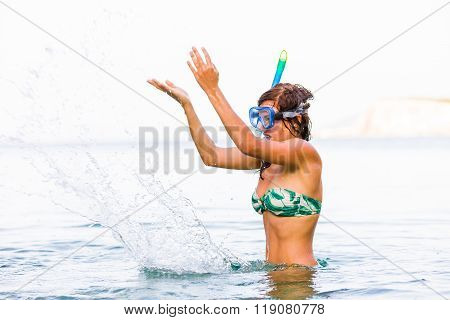 Playful woman splashing the seawater with snorkeling goggles and pipes on her head.