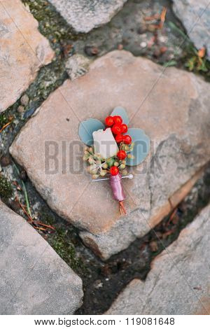 Vintage wedding boutonniere on the old pavement in the city center close up