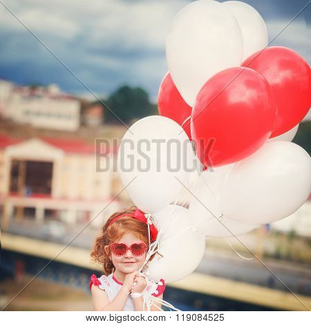 Little  Beautiful Curly Girl With Red And White Ballons In The P