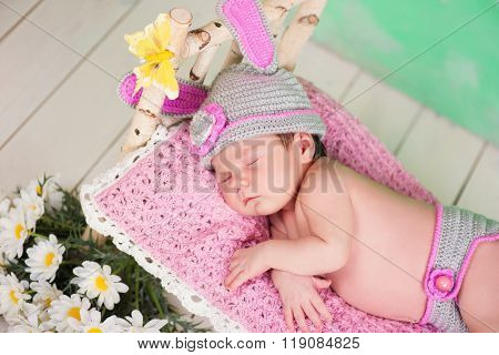 Newborn Baby Girl In A Knitted Hare Costume Sleeping On A Wooden Crib Birch