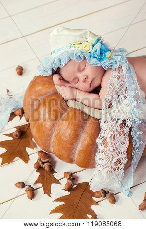 Tale Of Cinderella. Little Beautiful Newborn Baby Girl In A Bonnet Sleeping On A Pumpkin