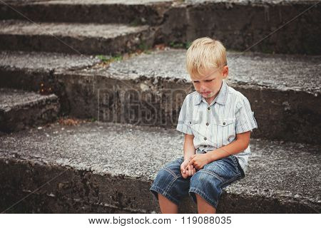Little Boy Crying  Sitting On Stone Steps In Park. Loneliness, M