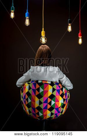 Woman sitting on the chair with illuminated colorful lamps