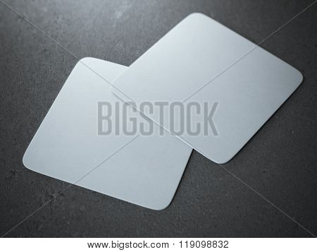 Two white square beer coasters
