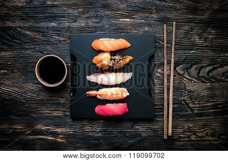 set of sashimi sushi with soy and chopsticks