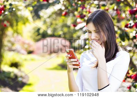 Beautiful Girl Reading Text Message On Her Smart Phone In The Garden