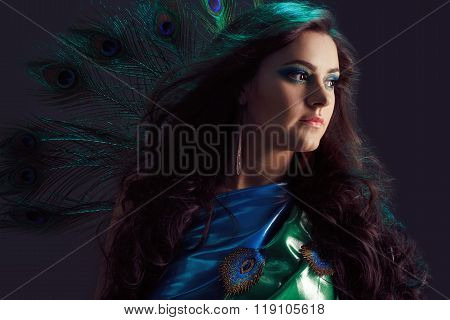 Woman in brilliant blue dress with peacock feathers design. Creative fantasy makeup, long dark hair