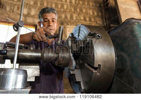Thai mechanic turner using machinery in his workshop, focus on the machine.