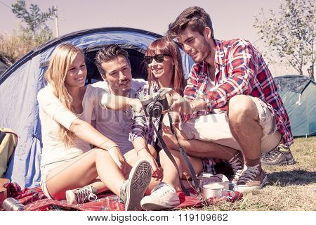 Group Of Young Adult Watching Photos On Digital Camera