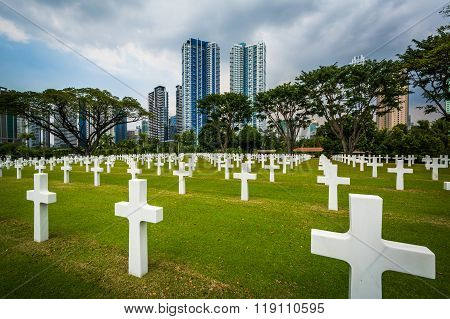 Graves And Modern Buildings In The Distance At The Manila American Cemetery & Memorial, In Taguig, M