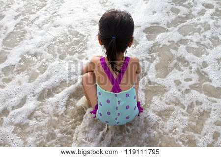 Asian Little Chinese Girl Sitting On The Beach