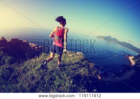 young fitness woman trail runner running on seaside