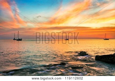 Yachts in the tropical sea at sunset