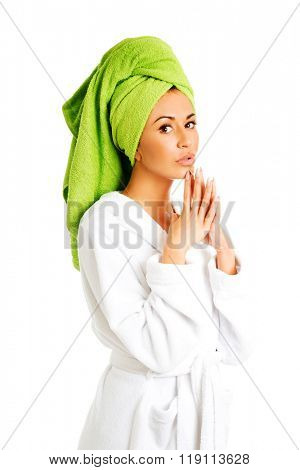 Woman in bathrobe clenching hands