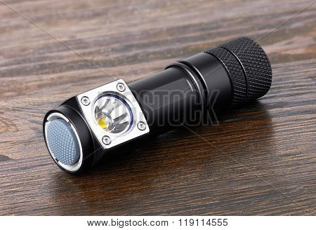 Flashlight, on wooden background, close-up