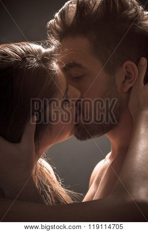 Sexy couple kissing in studio