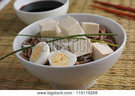 Soba noodle soup with boiled egg, tofu, daikon radish and green onion