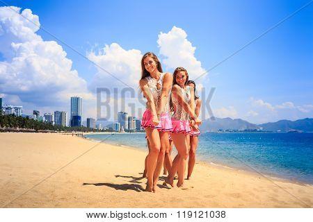 Cheerleaders Stand As Group Crossing Hands On Beach