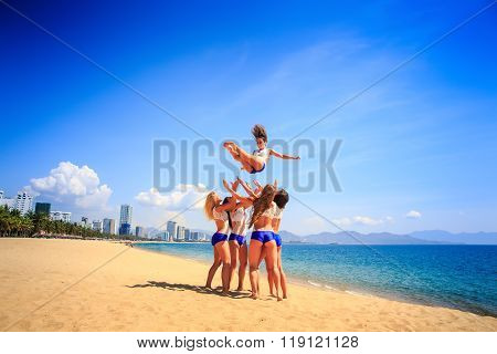 Cheerleaders Perform Tumbling Toss On Beach Against Azure Sea