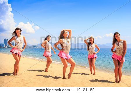 Cheerleaders Stand On Beach Hold Hands On Hip Against Azure Sea