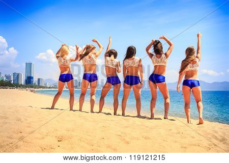 Cheerleaders Stand Backside View On Beach Against Azure Sea