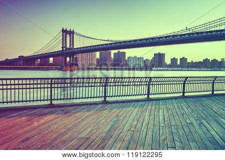 View of Manhattan Suspension Bridge Spanning the East River at Sunset with View of Manhattan from Boardwalk in Waterfront Brooklyn Park, New York City, New York, USA in Muted Tones of Green and Blue