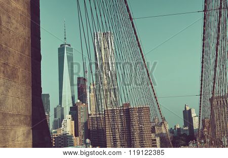 View of Manhattan Skyline Featuring One World Trade Center as seen through Cables and Archway of Historic Brooklyn Bridge in New York City, New York, USA