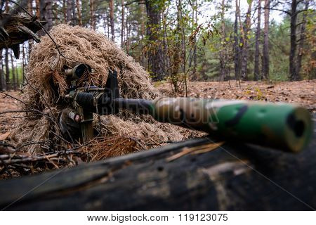 Soldier In Camouflage Suit With Sniper Rifle In Forest