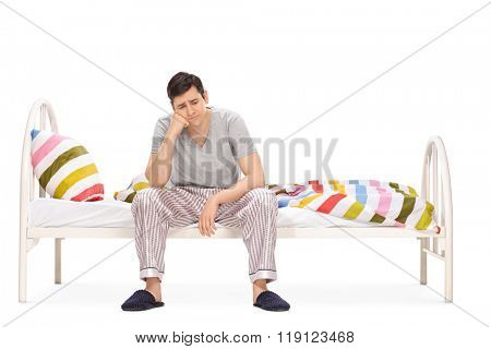 Sad young man sitting on a bed and contemplating isolated on white background