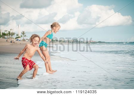 Sister And Brother Playing On The Beach At The Day Time.