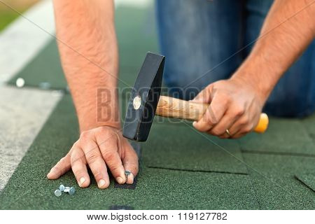 Worker Hands Installing Bitumen Roof Shingles - Horizontal Crop