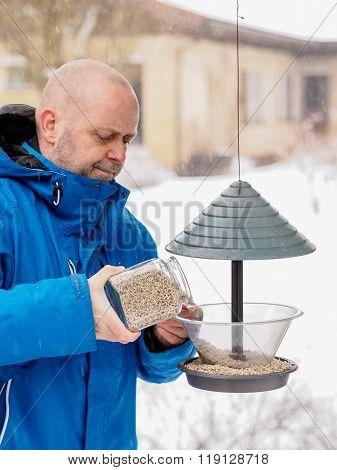 Man Fills A Bird Feeder