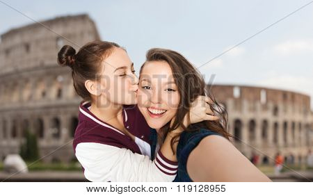 people, travel, tourism and friendship concept - happy smiling pretty teenage girls taking selfie and kissing over coliseum in rome background