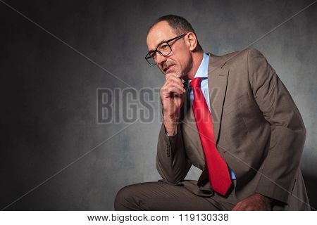 portrait of mature elegant businessman wearing glasses and looking away from the camera while thinking and posing in studio background