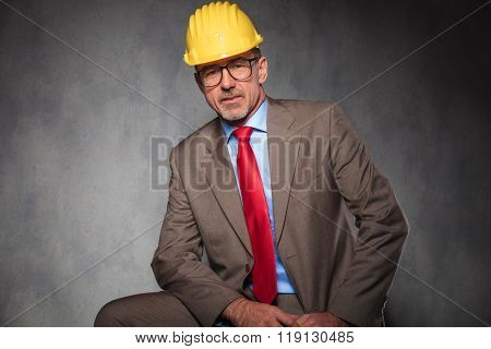 portrait of elegant senior engineer wearing glasses and helmet while posing seated in studio background