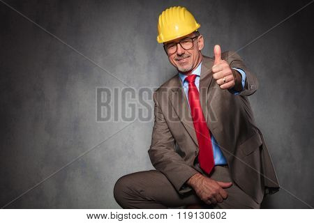 portrait of elegant engineer wearing helmet and glasses while seated and showing thumbs up in studio background