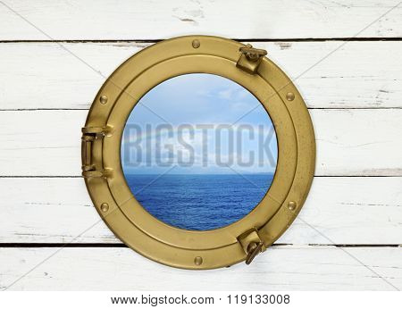 view through brass porthole to rainbow over island in blue sea
