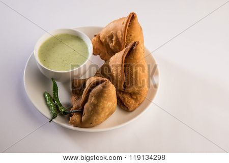 Indian snack samosa with green chutney and green fried chilli