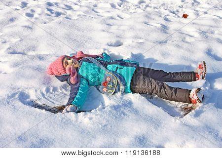 Little Girl Lying On A Snow