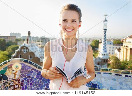 Woman With Tourist Guide Listening Audioguide In Park Guell