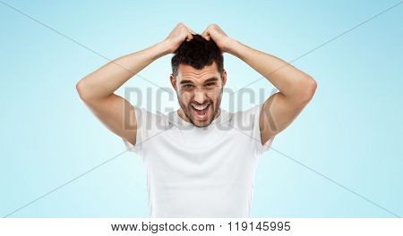 emotions, stress, madness and people concept - crazy shouting man rending ones hair in t-shirt over blue background