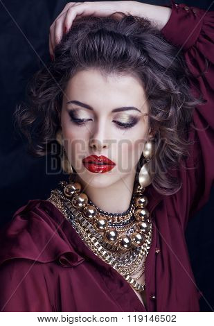 rich brunette woman with a lot of jewelery, hispanic curly hair red lipstick makeup