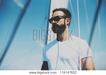 Low angle view of young bearded man standing on the yacht.