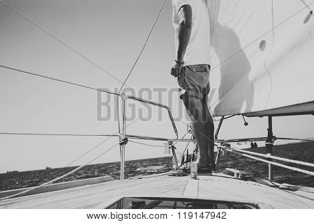 Low angle view of young bearded man standing on the yacht in sunny day. Horizontal black and white m