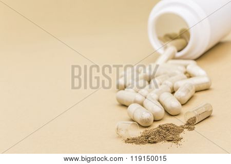 Pills Spilling From An Open Bottle On Brown Background
